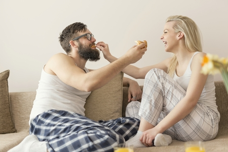 levantandose: Couple in love sitting on the couch in the living room, wearing pajamas after getting up in the morning, enjoying the morning and having breakfast