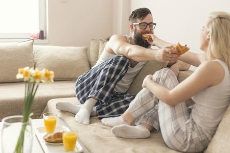 levantandose: Pareja en el amor que se sienta en el sof� de la sala de estar, con un pijama despu�s de levantarse por la ma�ana, disfrutando de la ma�ana y desayunar Foto de archivo