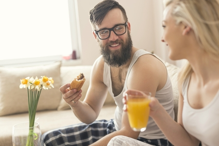 wakening: Couple in love sitting on the couch in the living room, wearing pajamas after getting up in the morning, enjoying the morning and having breakfast