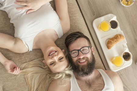 wakening: Top view of a young couple in love lying on a couch, getting up in the morning and having breakfast in bed
