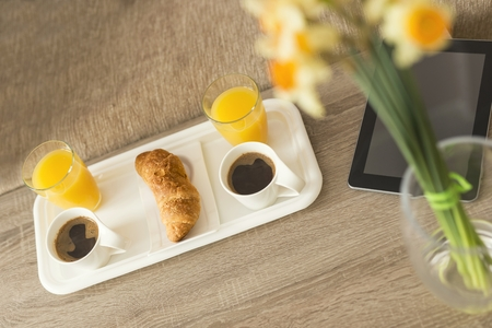 wakening: Top view of a breakfast tray on a table in a hotel room with tablet computer placed next to it Stock Photo