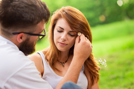 Couple sitting on a picnic blanket in a park. Guy gently placing flowers into girls hair