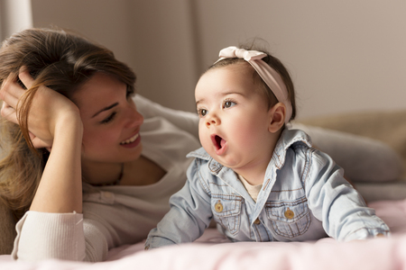 looking at baby: Beautiful baby girl and her mother lying in bed, playing and cuddling. Focus on the baby Stock Photo