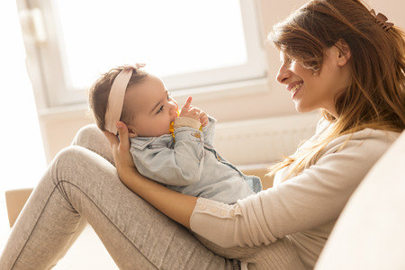 Young mother holding her baby girl in her arms, sitting on a living room couch next to a window, laughing and playing. Focus on the baby Stock Photo