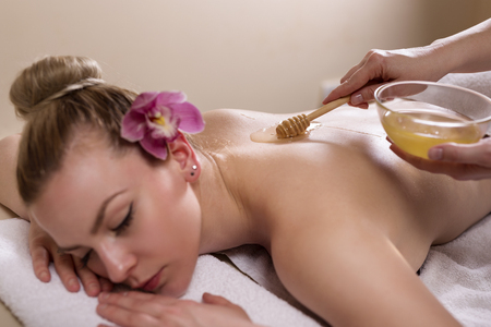 Woman lying in a beauty parlour, enjoying relaxing back massage and skin treatments with honey
