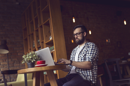 freelancing: Handsome hipster guy sitting in an armchair in a cafe, having a morning coffee and using a laptop computer for his freelancing job Stock Photo