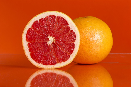 Studio shot of a cross section and whole grapefruit isolated on red background. Focus stacked image Stock Photo