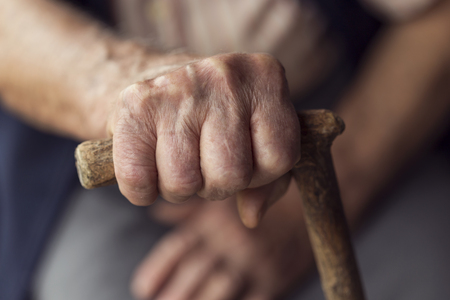 woman's hands: Detail of an elderly womans hands holding a cane. Selective focus