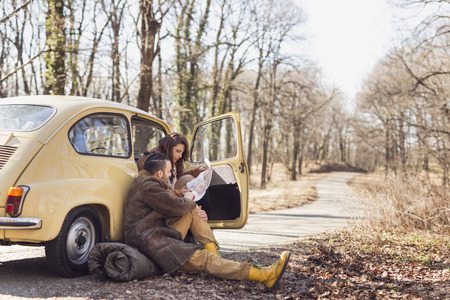couple dating: Young couple in love taking a break on their road trip, sitting by the road and looking at a map, trying to decide their route