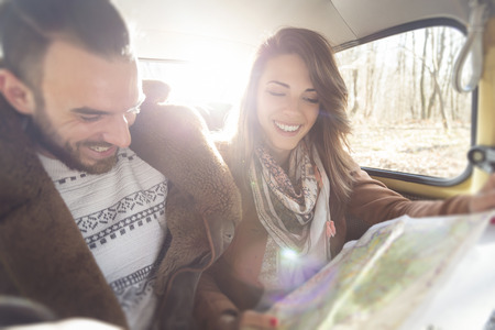 Young couple sitting in an old-timer car, reading a map, searching for directions for their road trip route Stock Photo