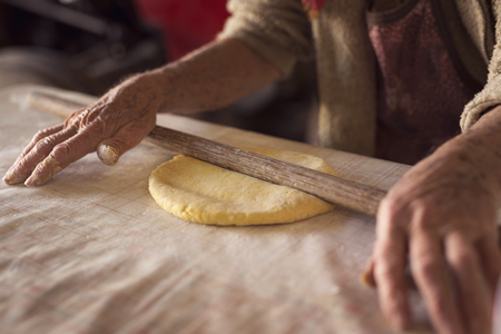 Detail of an elderly womans hand rolling out a dough with a rolling pin while making homemade pasta. Selective focus