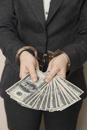 Business woman in a suit with handcuffs, arrested, offering bribery money for her releasing. Selective focus