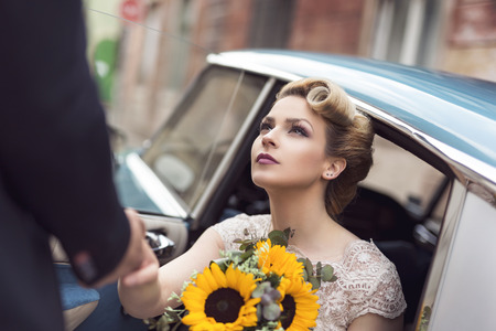 Beautiful young bride sitting in a wedding dress in a retro old car, holding a sunflower bouquet while groom is helping her get out of the car