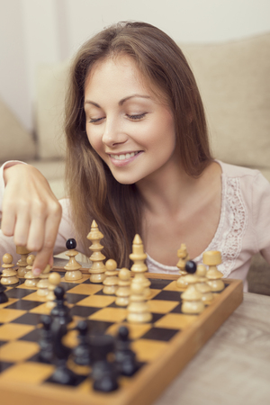 Portrait of a beautiful young woman smiling while making her move in a chess game