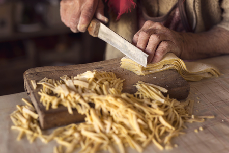 Detail of an elderly woman's hand cutting noodles with an old knife while making homemade pasta. Selective focus Stockfoto