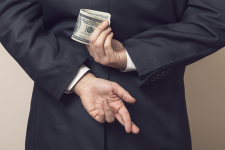 Businessman in a suit holding his hands behind his back with stack of dollar banknotes in one and fingers crossed on another one