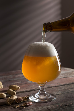 Detail of a glass of cold unfiltered pale beer being poured from a bottle, with some peanuts next to the glass. Selective focus Stock Photo