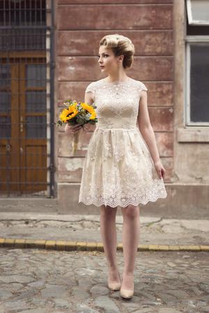 Het mooie jonge bruid stellen in een huwelijkskleding in een retro cobble straat, die een zonnebloemboeket houdt
