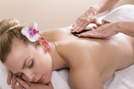 Woman lying in a beauty parlour, enjoying relaxing back massage with chocolate