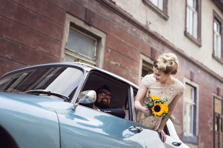 Young newlywed couple in a retro vintage car, groom driving while bride is waving through a window while they are leaving on their honeymoon. Focus on the bride