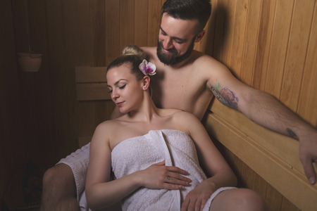 woman in bath: Young couple enjoying the sauna session together and relaxing Stock Photo