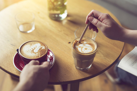 Top view of two people holding a nicely decorated latte art coffee cups, enjoying their morning coffee. Selective focus