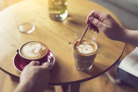Hoogste mening van twee mensen die een keurig verfraaide latte kop van de kunstkoffie houden, die van hun ochtendkoffie geniet. Selectieve aandacht