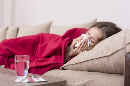 headaches: Sick woman covered with a blanket lying in bed with high fever and a flu, blowing her nose. Pills and glass of water on the table