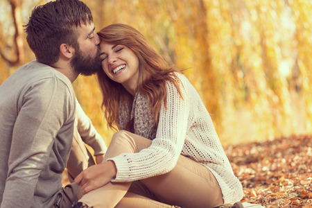 Couple in love sitting on autumn fallen leaves in a park, enjoying a beautiful autumn day. Man kissing a woman in a forehead