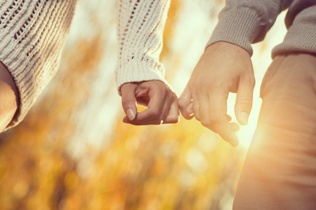 Detail of a young couple in love holding hands and walking through a park on a sunny autumn day. Selective focus Stock Photo