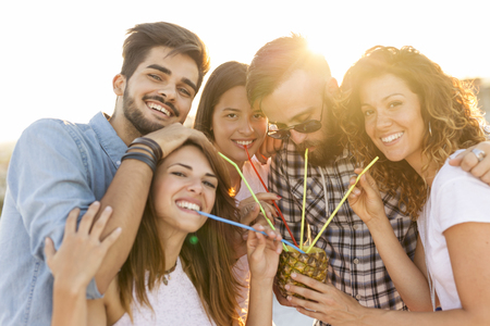 Group of young friends having fun at rooftop party, drinking a pineapple cocktail. Focus on the couple in the middle