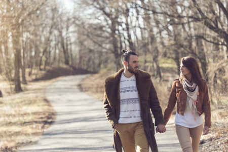 Couple holding hands and walking down the road through a forest, enjoying a sunny spring day Stock Photo