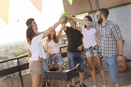 Group of young friends having fun at rooftop party, making barbecue, drinking beer and enjoying hot summer days. Focus on the people in the middle Stockfoto