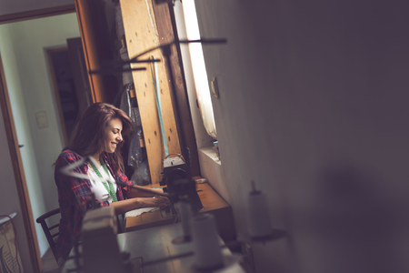 sewing machines: Seamstress sitting at a sewing machine and sewing in a workshop Stock Photo