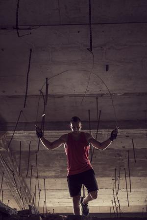 Jong atletenentouwtjespringen bij een verlaten gebouw, het uitwerken Stockfoto