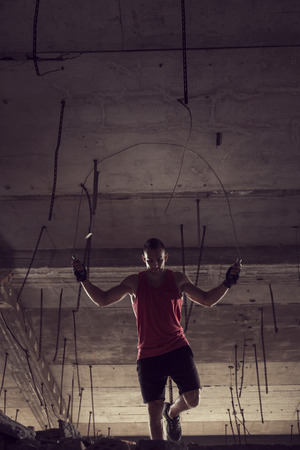 Young athlete jumping rope at an abandoned building, working out