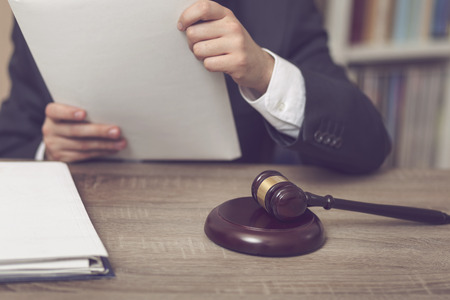 Detail of a judge sitting at his desk, holding a file with a new case and studying it. Selective focus Stock Photo