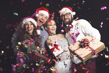 Two couples having fun at New Years party and holding nicely wrapped present boxes