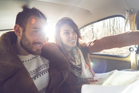 Young couple having fun and enjoying a road trip both sitting at the back seat of a car and reading the map in search of the right direction. Focus on the girl
