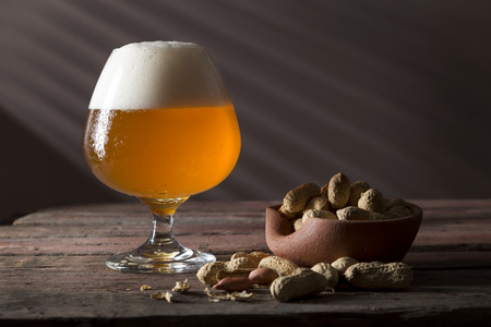 Glass of cold light unfiltered beer and a bowl of peanuts on a rustic wooden pub table. Focus on the froth Imagens