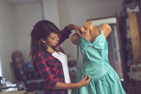 若いファッション デザイナーの作業彼女のアトリエでの新しいドレスについて測定テープの措置を講ずること
