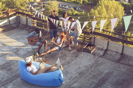 Group of young friends having a rooftop party, playing the guitar and enjoying hot summer days Stock Photo