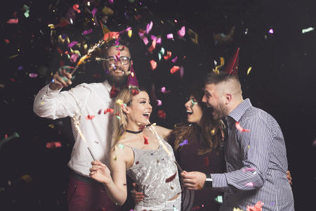 Two beautiful young couples having fun at New Year's party, wearing party hats, holding firework sprinkles and dancing
