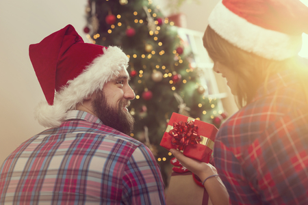 Beautiful young couple in love sitting on a living room floor next to a nicely decorated Christmas tree and exchanging presents