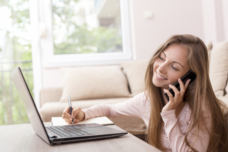 Young female student studying and exchanging notes with her colleagues using modern technologies, having a phone conversation and taking notes Stock Photo