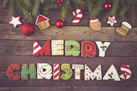stock photo table top shot of colorful gingerbread cookies shaped like letters merry christmas and christmas tree decorations on fir tree branches - Gingerbread Christmas Tree Decorations