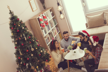 Young friends sitting on the living room floor next to a Christmas tree on a Christmas morning, drinking coffee. Focus on the couple next to the tree