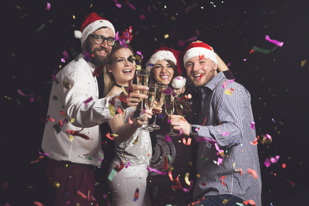 Four young friends on a New Year's eve party making a toast raising glasses of champagne at midnight