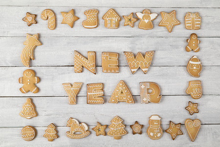Table top shot of a frame made of nicely decorated gingerbread cookies with New Year written within the frame Фото со стока