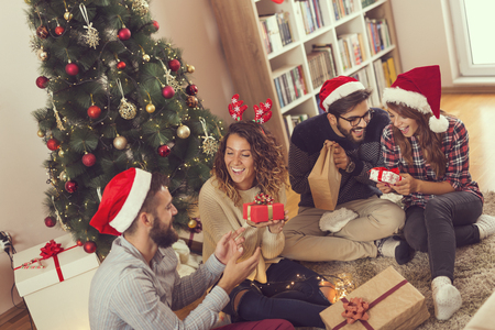 Group of young friends sitting next to a nicely decorated Christmas tree, exchanging Christmas presents. Focus on the girl wearing antlers